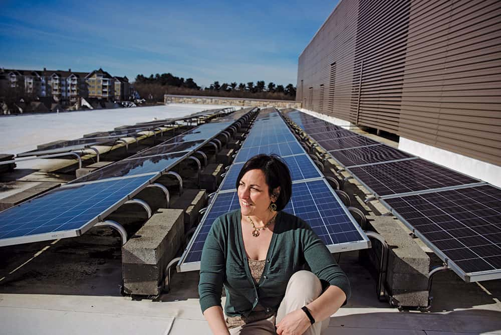 Leah Miller, Energy Manager of the Office of Community Sustainability,  on the solar paneled roof of the Miller Library (no relation).