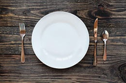 Empty white dinner plate over a rustic wooden table