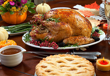"Roasted pepper turkey for Thanksgiving, garnished with pink pepper, blackberry, and fresh rosemary twigs on a dinner table decorated with mini pumpkins, beans, carrots, baked potato, pie, cranberry relish, gravy, flowers, candles, and flutes of champagne.""n"