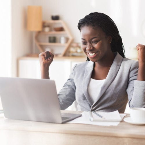 Business Success. Excited African Businesswoman Celebrating Success At Workplace, Raising Hands And Looking At Laptop, Panorama With Free Space